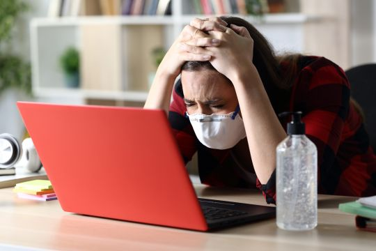 Sad student woman with protective mask in coronavirus quarantine checking laptop sitting on a desk at home